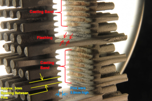 "Heat exchanger cross section showing deposits of sand remaining from casting process packed between the 3.0mm high interval fins. ""Sand Cast"" surface indicates insignificant corrosion has occurred."